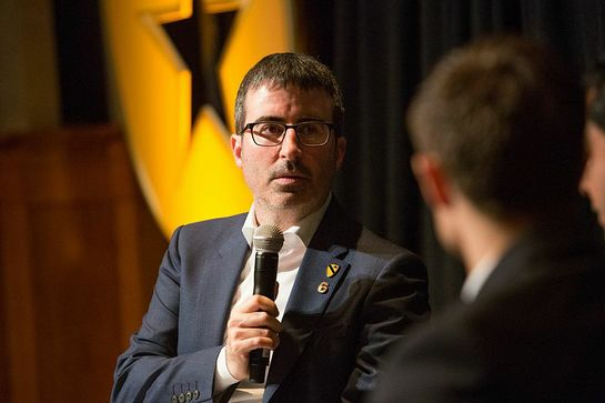 Comedian John Oliver interviewing a veteran on stage during the second annual Got Your 6 Storytellers event