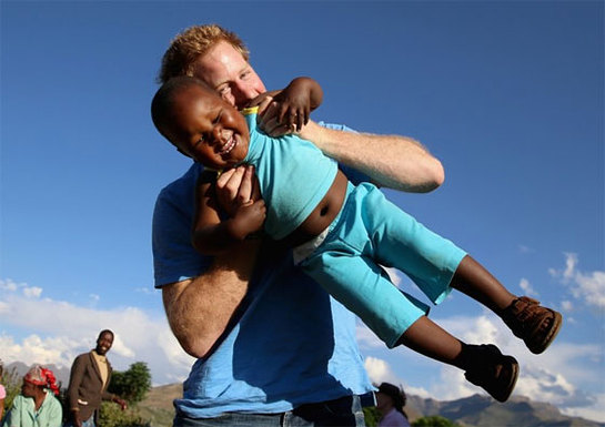 Prince Harry swings a child in the air in Lesotho