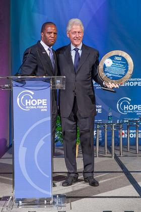 Operation HOPE Founder John Hope Bryant presents award to President Bill Clinton at the 2015 HOPE Global Forum