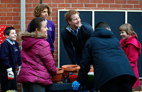 Prince Harry laughs with youngsters involved in a garden project during a visit to the Full Effect Youth Projec