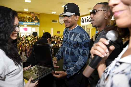 Chance the Rapper and Ludacris present a new Internet Essentials laptop to an Alcott College Prep student for the Get Schooled, Get Connected Spring Challenge.