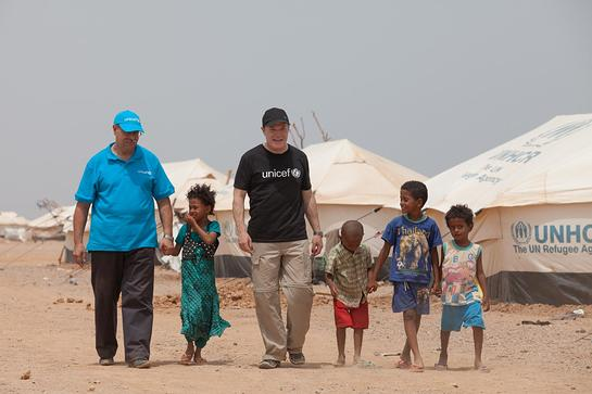 Eddie Izzard and UNICEF Djibouti Deputy Representative Moncef Moalla with refugees from Yemen