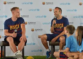 Marc-Andre ter Stegen and Andres Iniesta speak with children during an an event organized by FC Barcelona and UNICEF