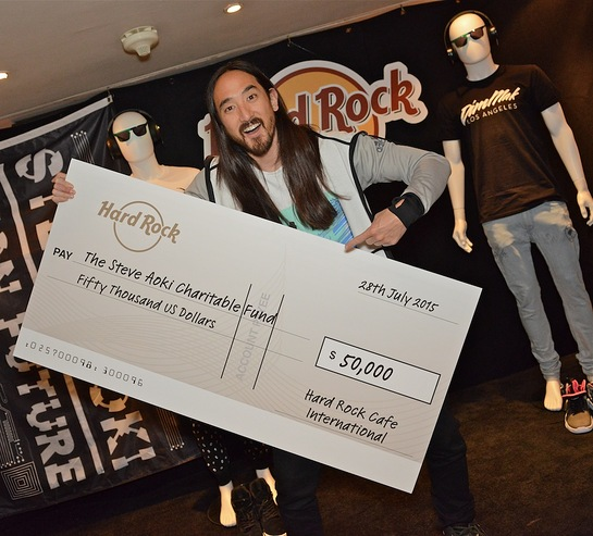 American electro house musician Steve Aoki accepts a $50,000 check