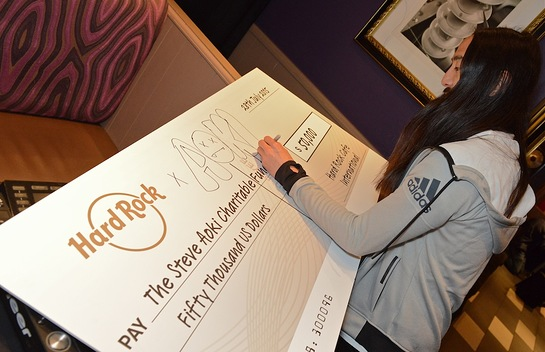 Steve Aoki signs the $50,000 check to the Steve Aoki Charitable Fund, presented by Hard Rock International
