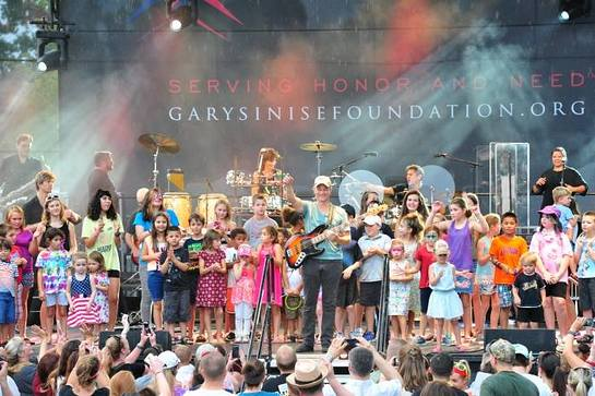 Gary Sinise was joined on stage by the young children of the troops at Fort Belvoir during the USO-Metro Invincible Spirit Festival