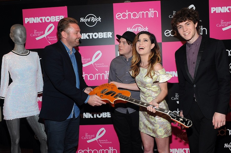 James Buell, left, Senior Director of Music and Marketing for Hard Rock International, accepts a signed guitar from Echosmith