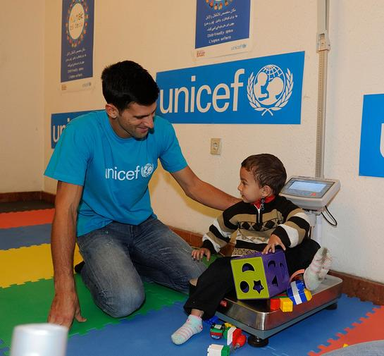 Novak Djokovic plays with a boy at the UNICEF-supported child friendly space in Belgrade