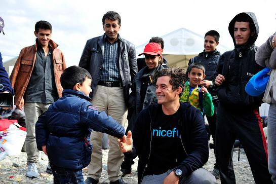 Orlando Bloom greets a child at the refugee and migrants reception centre near the town of Gevgelija, close to the border with Greece.