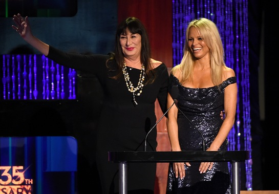 Anjelica Huston (L) and actress Pamela Anderson speak onstage at PETA's 35th Anniversary Party at Hollywood Palladium
