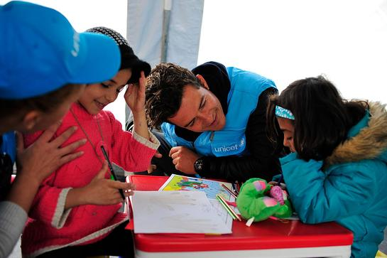 Orlando Bloom greets children in a child-friendly space at the refugees and migrants one stop registration centre in the town of Presevo in south Serbia